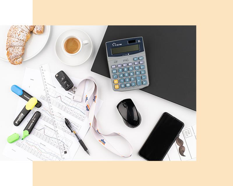 Flatlay contabilità: calcolatrice, evidenziatore, chiavi macchina, laptop