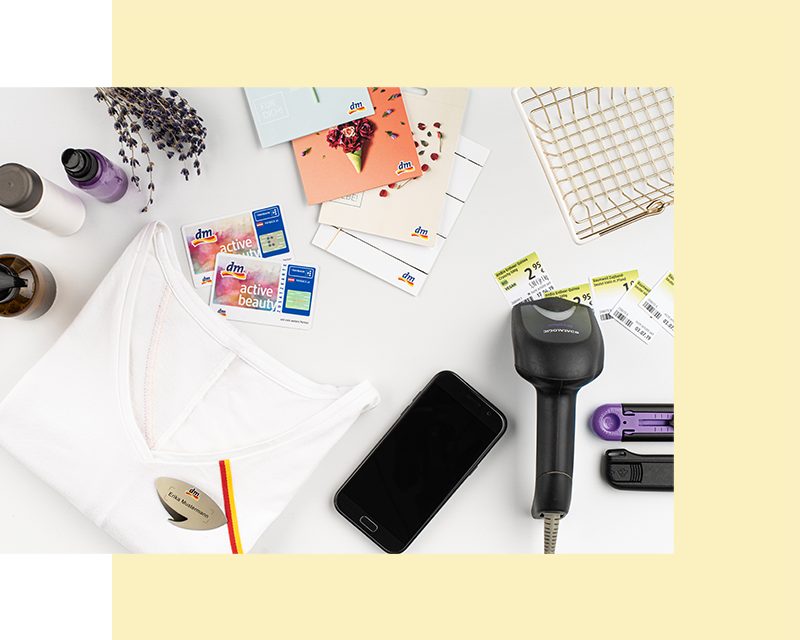 Flatlay per filiali: t-shirt di lavoro, scanner cassa, smartphone