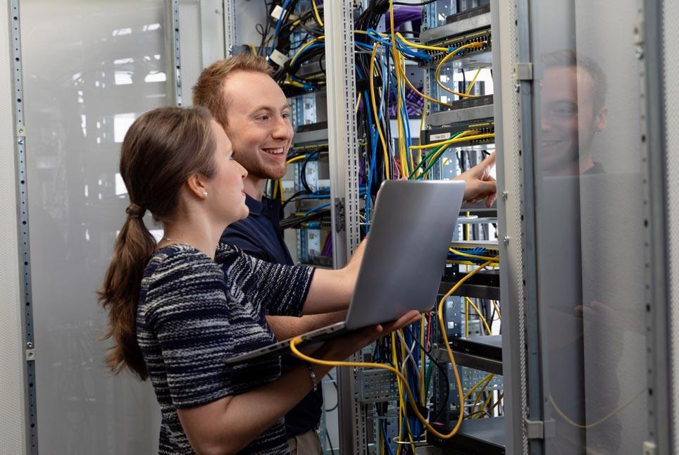 IT-Lehrling mit Lernbegleiter am Netzwerkschrank